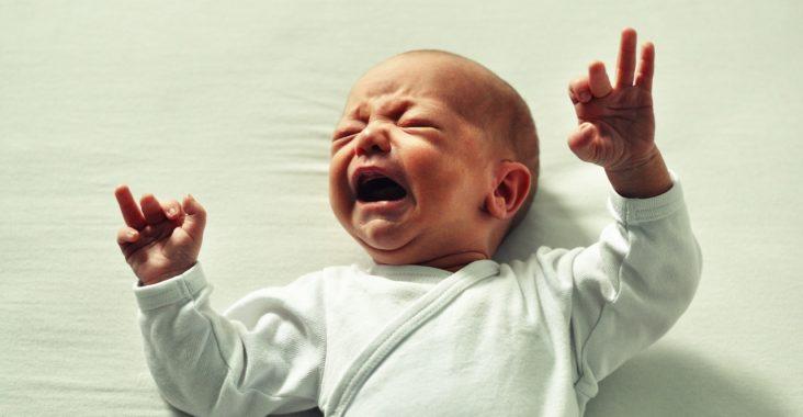 niemowlę płacze położone w łóżku