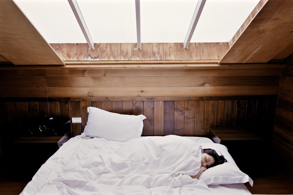 kobieta śpi w łóżku w drewnianym domu, zdrowy sen, teoria snu,