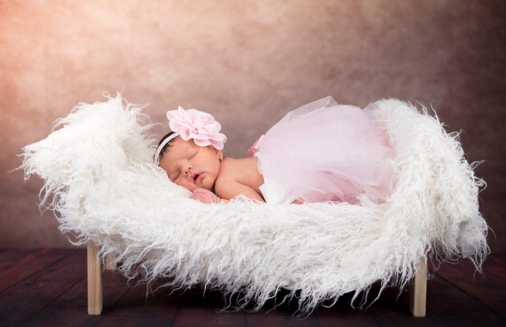 niemowlę śpi na futrze, dziewczynka w różowej opasce i tiulowej spódniczce