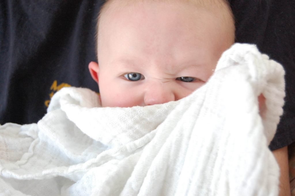 niemowlę zasłania się pieluszką i krzywi się