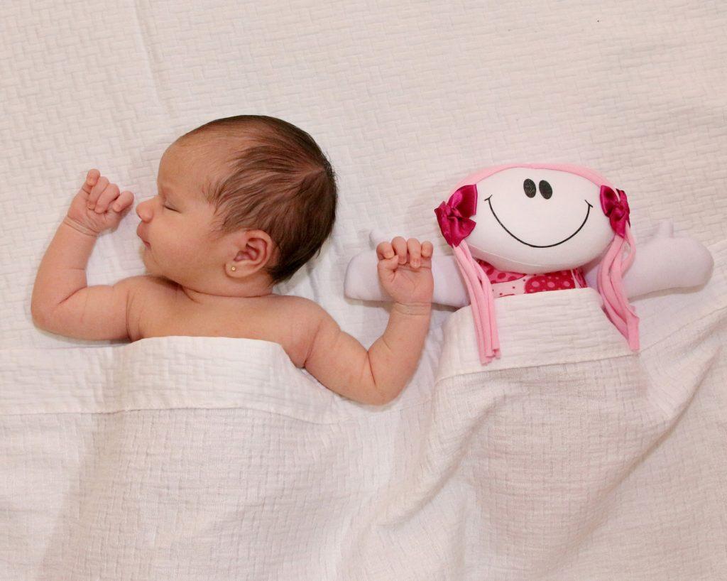 niemowlę dziewczynka śpi pod kołdrą razem z pluszową lalką