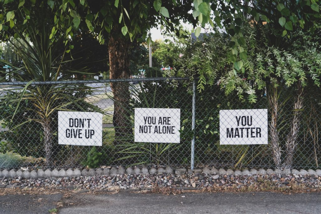 """Cheering up photo: 3 signs on the fence that say """"do not give up"""" """"You are not alone"""" """"you matter"""""""