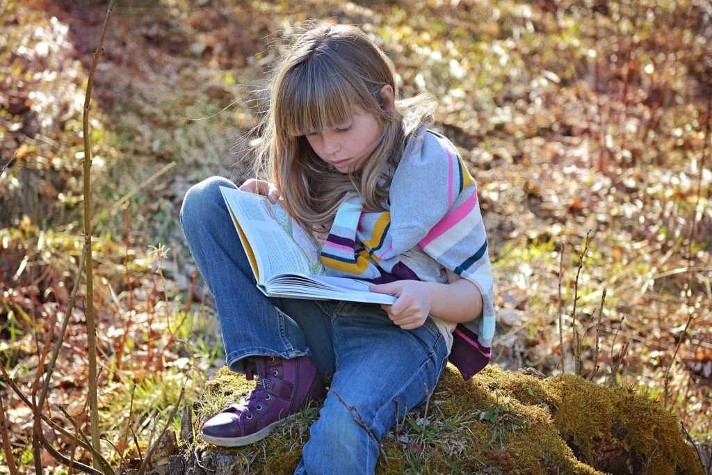 girl (about 10 years old) read the book in the forest.