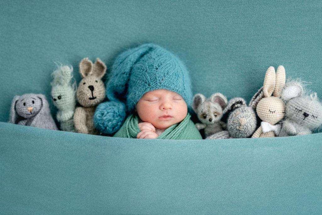 sesja noworodkowa, noworodek śpi pod kołdrą z pluszakami